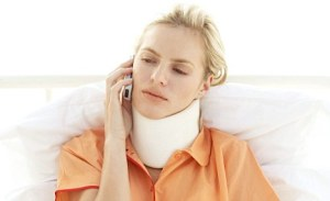 ANY249 Young woman lying in bed wearing a neck brace and an arm cast talking on a mobilephone